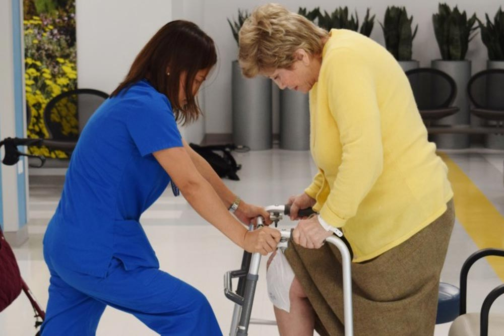 Physical therapist assisting senior female patient with exercises at Fordham Nursing Center.