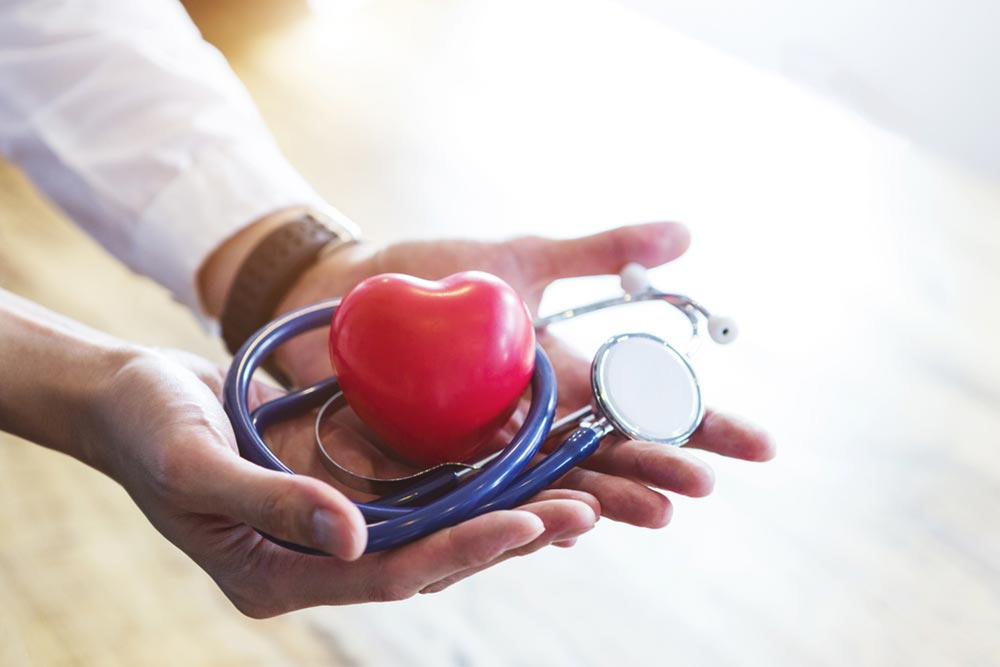 Doctor holding stethoscope and red heart on hands with white space. Healthcare concept.