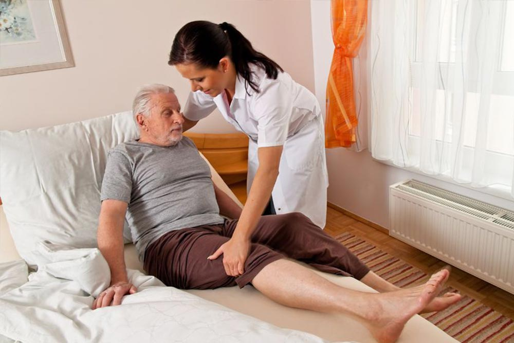 Young nurse helping a senior male patient to rise from his bed.