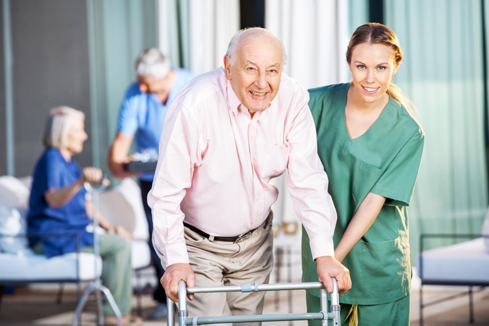Portrait of happy female caretaker helping senior man in using Zimmer frame at nursing home yard